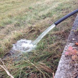 Slangen sprutar vatten från dammen